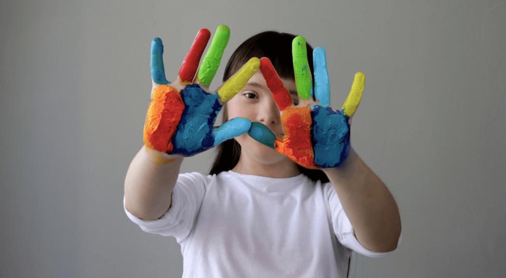 student with rainbow painted hands